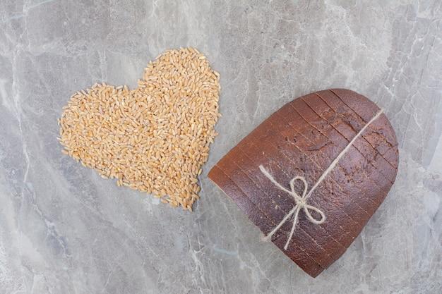Tranches de pain brun avec des grains d'avoine sur une surface en marbre