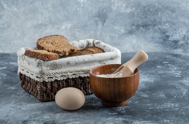 Tranches de pain brun sur un panier sur un mur gris.
