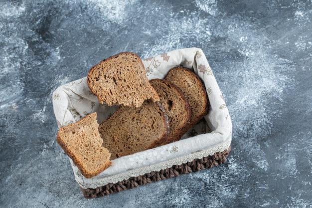 Tranches de pain brun sur un panier sur une surface grise.
