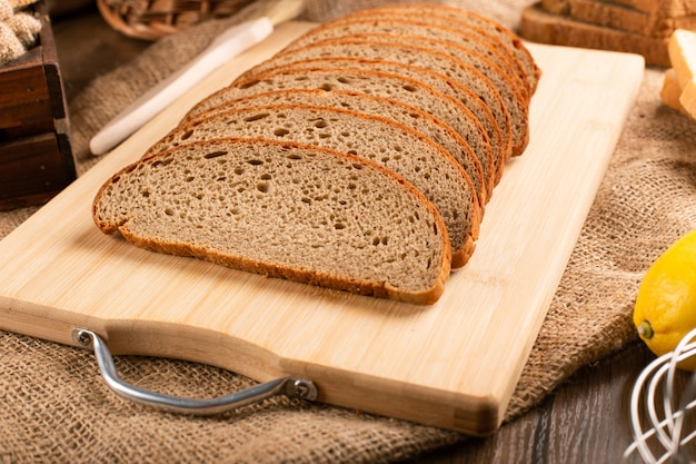 Tranches de pain brun sur planche de cuisine