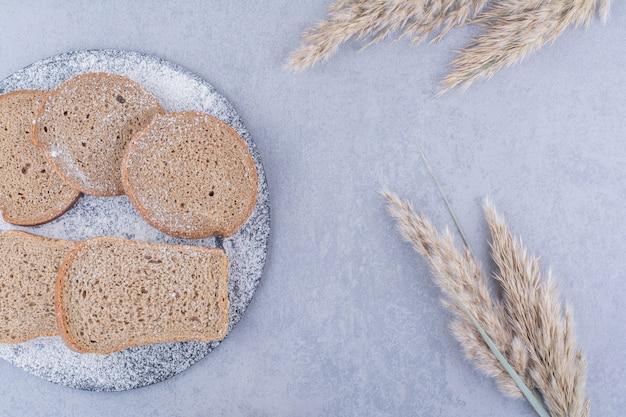 Tranches de pain brun sur une planche recouverte de farine à côté de tiges d'herbe de plumes sur la surface en marbre