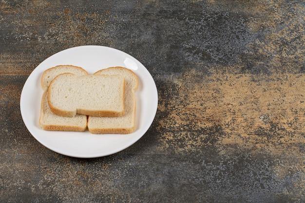 Tranches de pain brun sur plaque blanche.