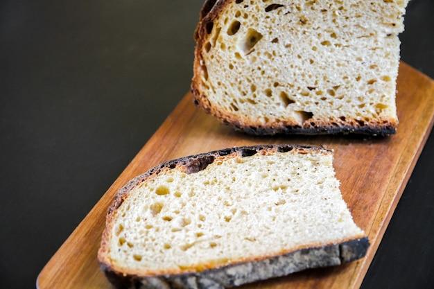 Tranches de pain de campagne traditionnelle française sur une planche à découper en bois