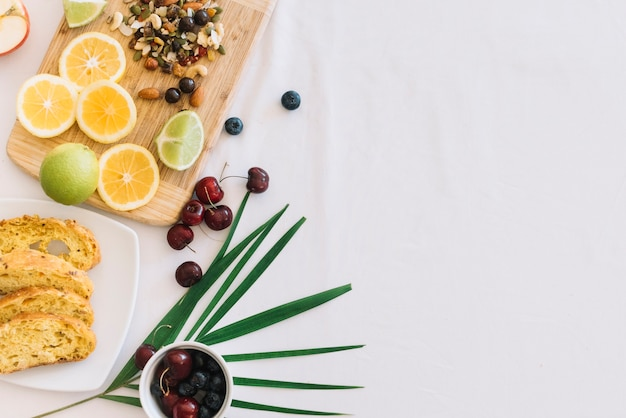 Tranches de pain; cerise; citron et fruits secs sur fond blanc