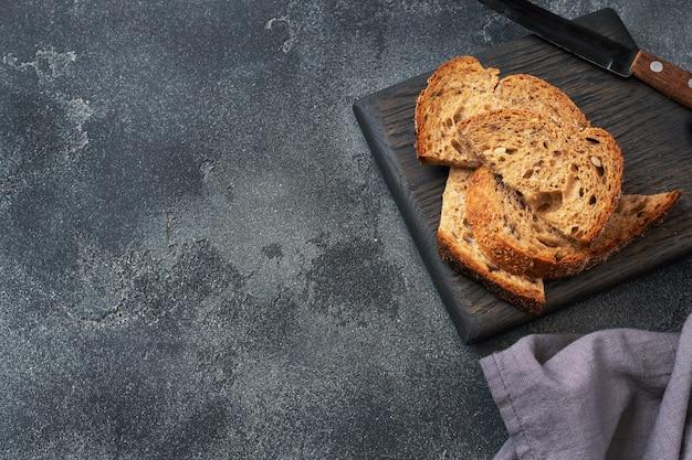 Tranches de pain complet sur une planche à découper en bois. fond de béton foncé. espace copie