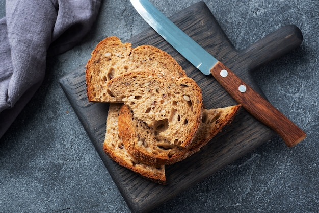 Tranches de pain complet sur une planche à découper en bois. fond de béton foncé.