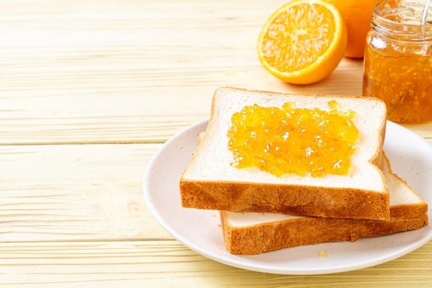 Tranches de pain avec de la confiture d'orange pour le petit déjeuner