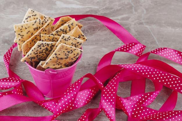 Tranches de pain dans un petit seau à côté d'un paquet de rubans sur marbre
