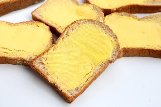 Tranches de pain avec du beurre sur table blanche.