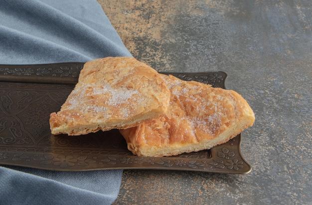Tranches de pain feseli sur un petit plateau orné sur bois.