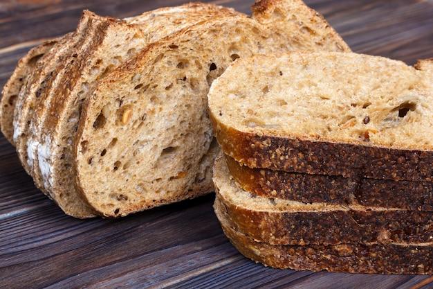 Tranches de pain frais sur une planche à découper sur un fond en bois blanc