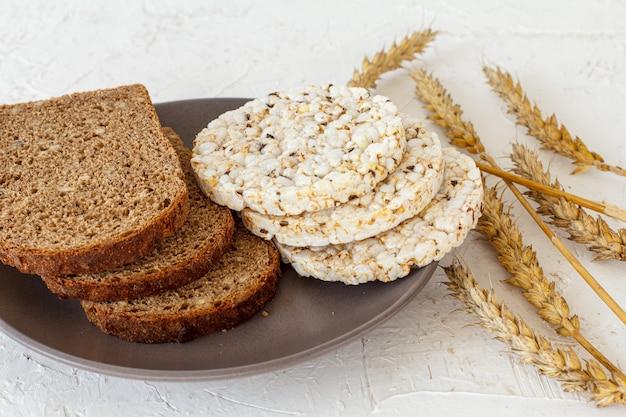 Tranches de pain et galettes de riz soufflé sur l'assiette, épillets de blé sur fond blanc structuré. vue de dessus.