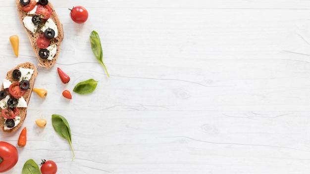Tranches de pain garnies de tomates; fromage et olives sur table blanche