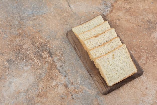 Tranches de pain grillé blanc sur planche de bois