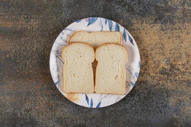 Tranches de pain grillé sur plaque colorée.