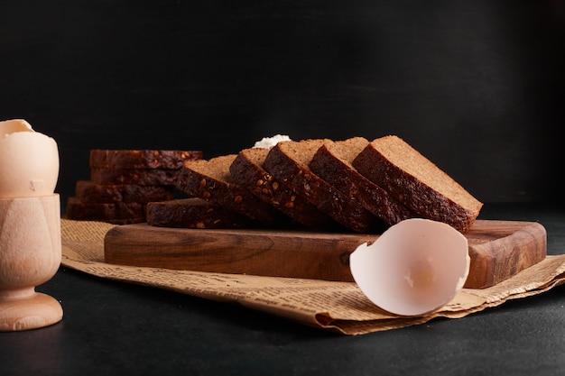 Tranches de pain avec des ingrédients sur la planche de bois