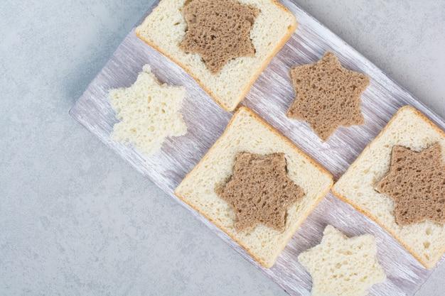 Tranches de pain noir et blanc en forme d'étoile et de carré sur une plaque en bois. photo de haute qualité