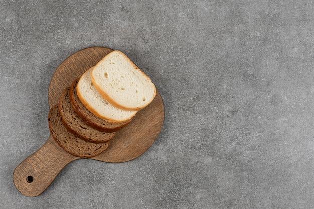 Tranches de pain noir et blanc en planche de bois