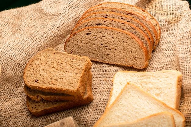 Tranches de pain noir et blanc sur la planche de la cuisine