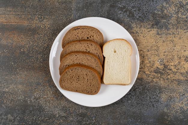Tranches de pain noir et blanc sur plaque blanche