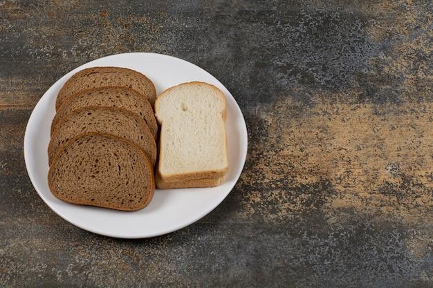 Tranches de pain noir et blanc sur plaque blanche.