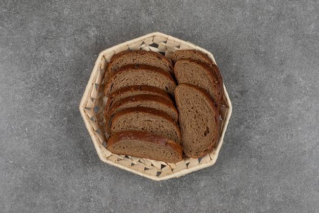 Tranches de pain noir dans un panier en bois.