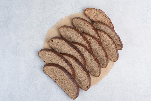 Tranches de pain noir sur feuille de papier