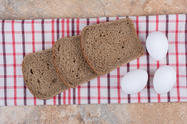 Tranches de pain noir sur nappe avec des œufs