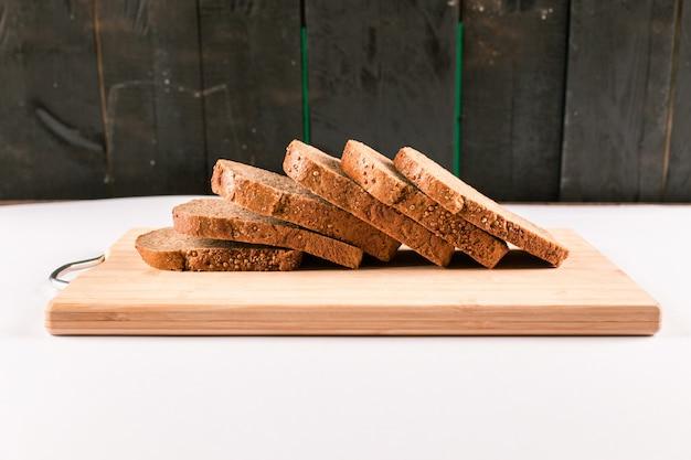 Tranches de pain noir sur planche de bois isolé sur fond noir
