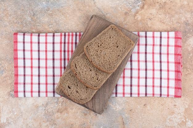 Tranches de pain noir sur planche de bois avec nappe