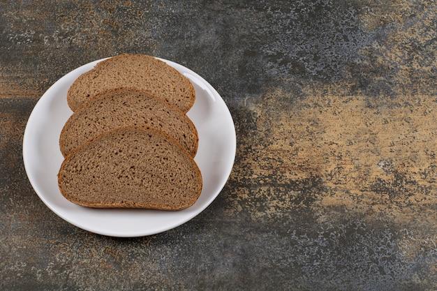 Tranches de pain noir de seigle sur plaque blanche