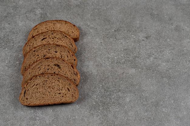 Tranches de pain noir sur une surface en marbre