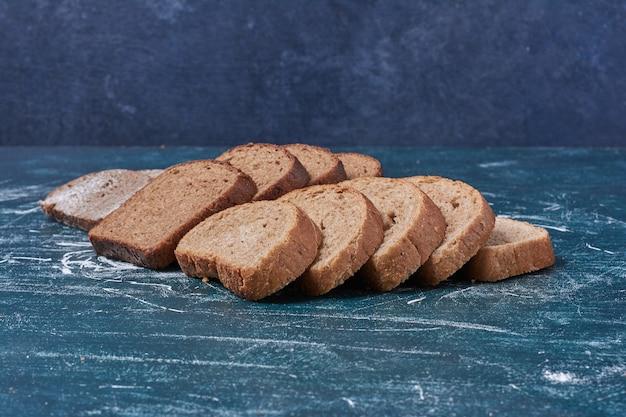 Tranches de pain noir sur table bleue.