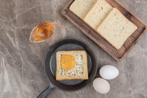 Tranches de pain, œufs et huile sur table en marbre. photo de haute qualité