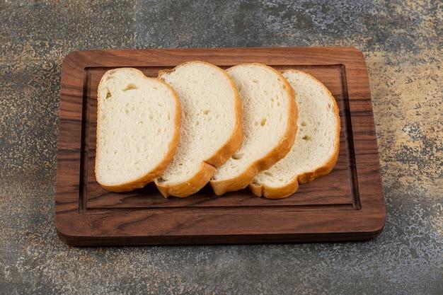 Tranches de pain parfumé sur planche de bois.