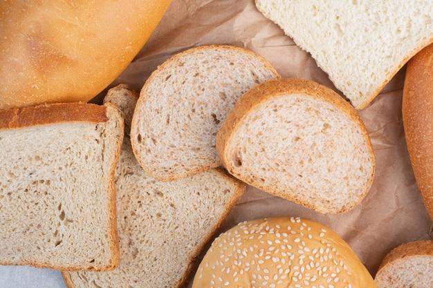 Tranches de pain et petit pain aux graines de sésame sur une feuille de papier