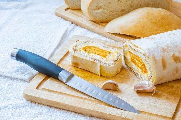 Tranches de pain pita arménien avec garniture de carottes sur une planche de bois. sur le plateau se trouvent des gousses d'ail et un couteau.