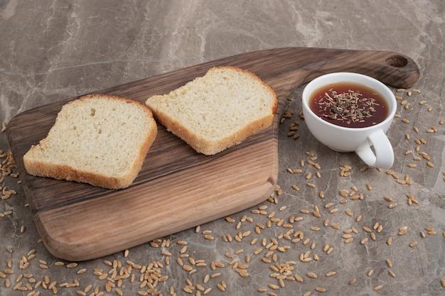 Tranches de pain sur une planche à découper avec une tasse de thé. photo de haute qualité