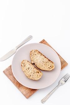 Tranches de pain sur plaque et espace de copie de la coutellerie