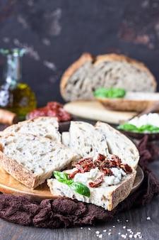 Tranches de pain à la ricotta, aux tomates séchées et au basilic servies sur une planche à découper en bois. bruschetta à la ricotta, tomates séchées et basilic.