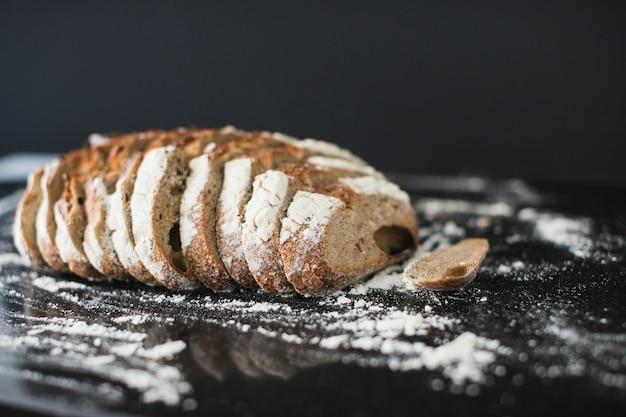 Tranches de pain rustiques avec de la farine saupoudrée sur un comptoir de cuisine réfléchissant
