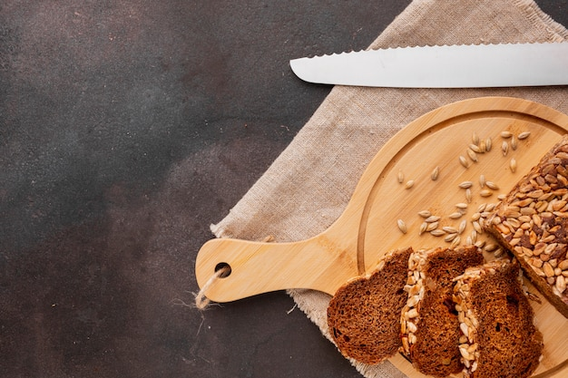 Tranches de pain sur sanglier en bois avec graines et couteau
