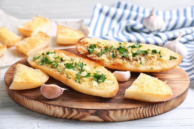 Tranches de pain savoureuses à l'ail, au fromage et aux herbes sur une planche à découper en bois