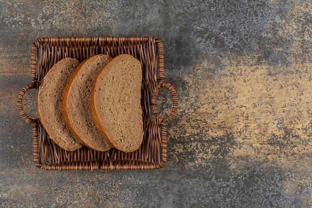Tranches de pain de seigle dans un panier en bois.