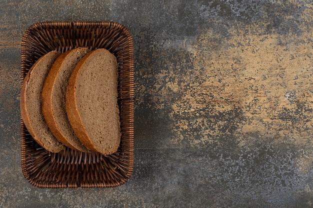 Tranches de pain de seigle frais dans un panier en bois