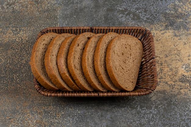 Tranches de pain de seigle frais dans un panier en bois.