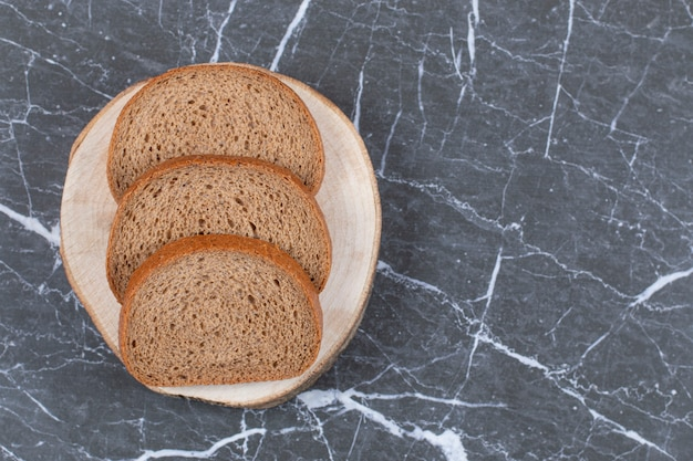 Tranches de pain de seigle sur une planche à découper sur fond gris.