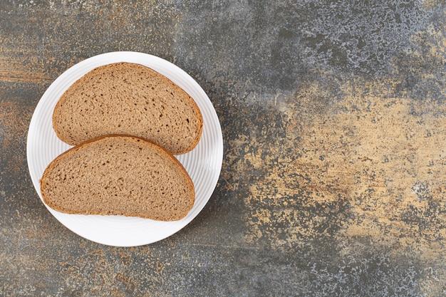 Tranches de pain de seigle sur plaque blanche