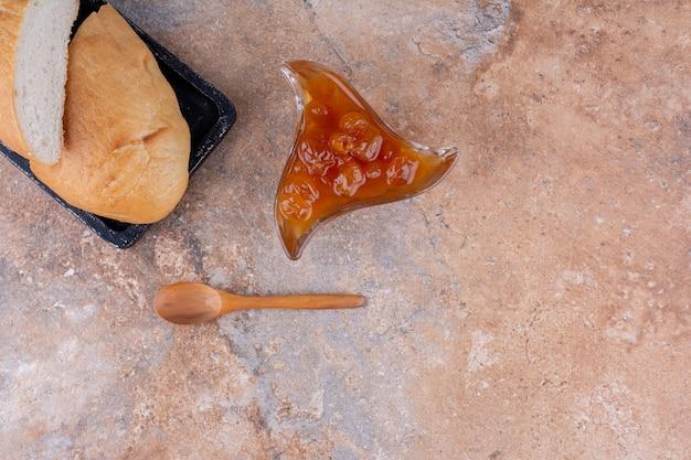 Tranches de pain avec une tasse de confiture de figues