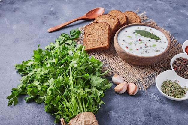 Tranches de pain avec une tasse de soupe au yogourt.